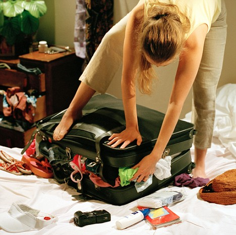 young woman standing on over packed suitcase in bedroom
